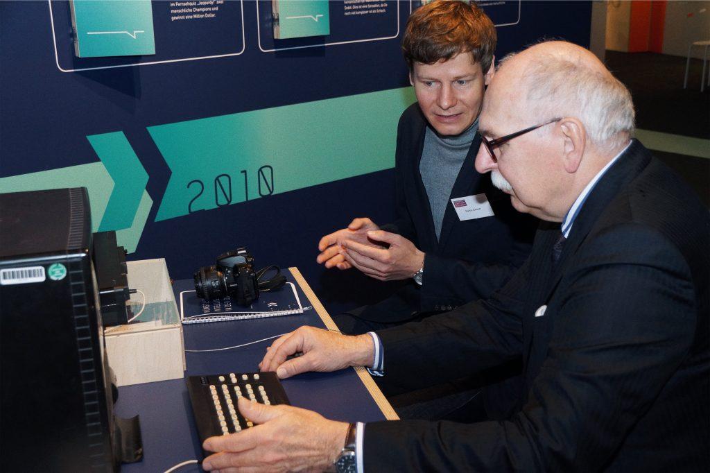 Projektmitarbeiter Martin Schmitt erläutert dem Präsidenten der Leibniz-Gemeinschaft Matthias Kleiner die Geschichte der künstlichen Intelligenz in der DDR.
